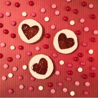 Cute Valentine's Day Cookies on a red background surrounded by candies