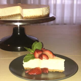 Delicious New York Style Cheesecake slice on a gray plate with cheesecake in the background