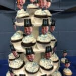 Chocolate cupcakes with white buttercream frosting, blue sprinkles and Carlos' face picture topper on a cupcake tower.