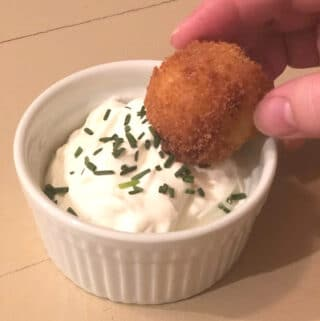 Loaded Mashed Potato Bite being dipped in sour cream