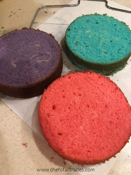 3 cakes. Pink, Purple, and Teal on parchment paper.