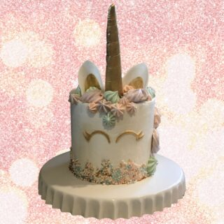 unicorn cake from cake tutorial on a white platter with a glitter background.