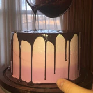 Silky Smooth Chocolate Ganache being pour over a pink cake