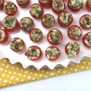 Bacon Stuffed Cherry Tomatoes on and white platter on a yellow and white tea towel