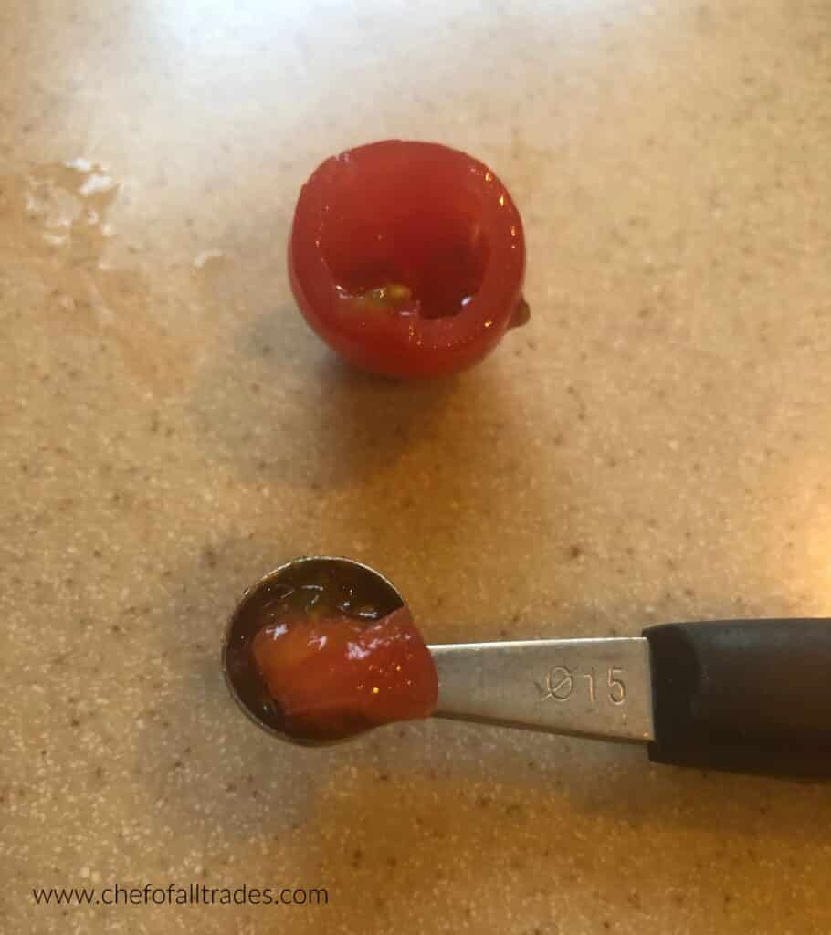 melon baller scooping pulp and seeds from tomatoes