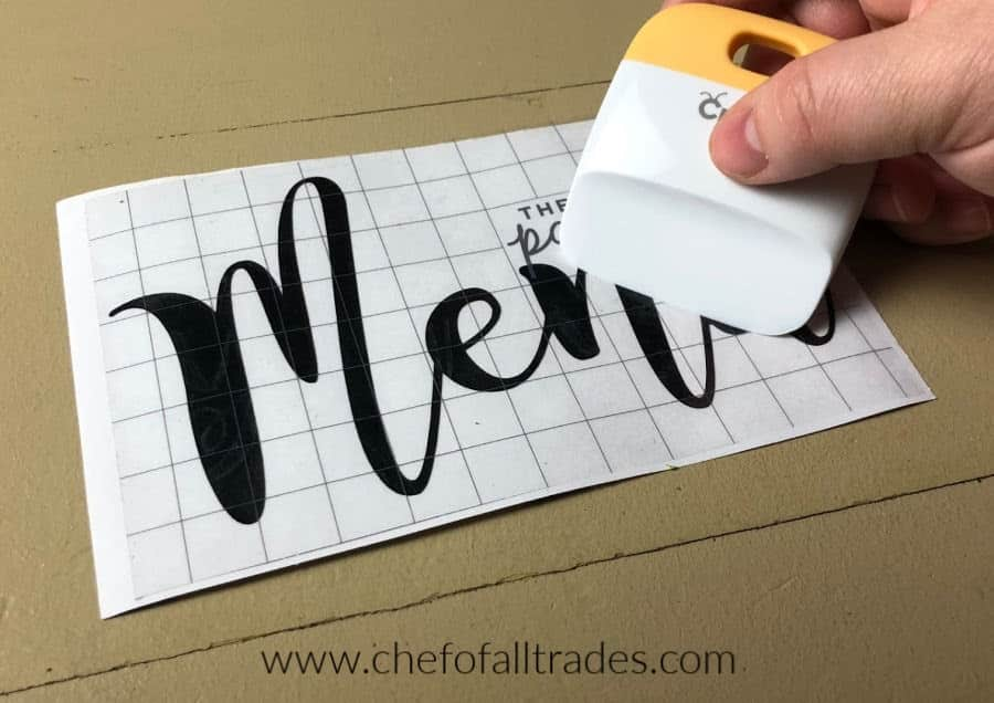 Using a scraper to transfer vinyl to transfer tape.