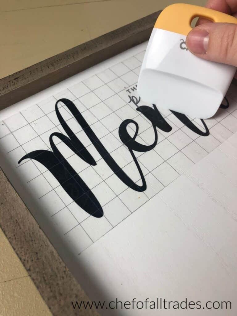 using a scraper to attach the vinyl to the menu board