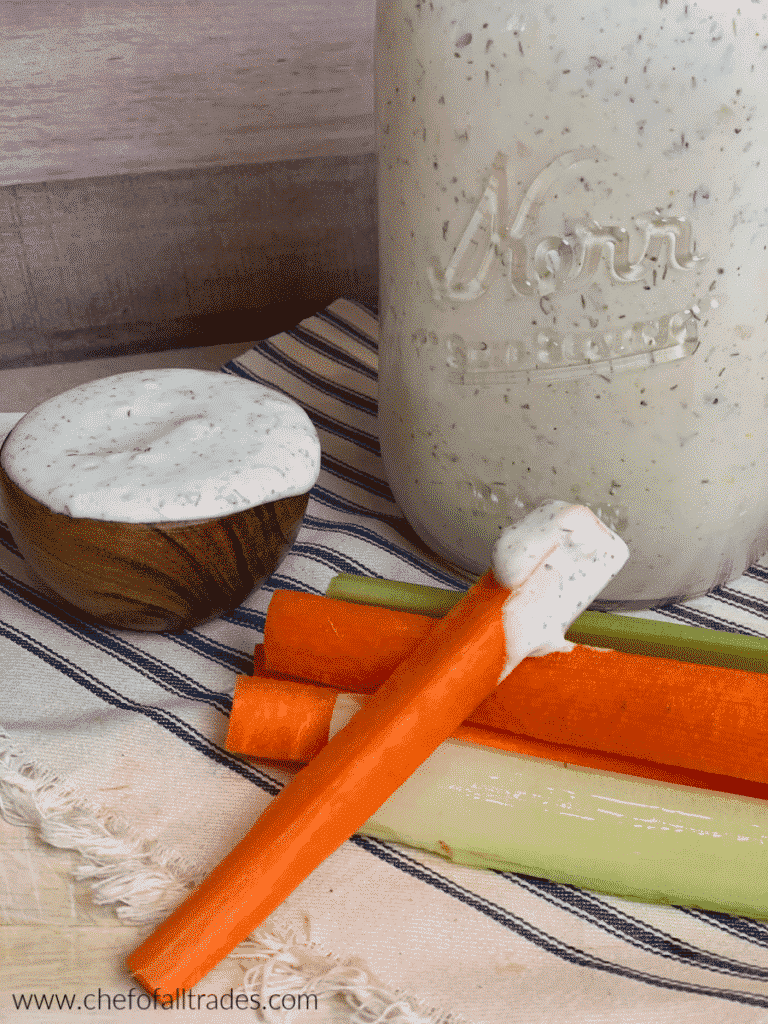 Ranch in a mason jar with carrot and celery sticks