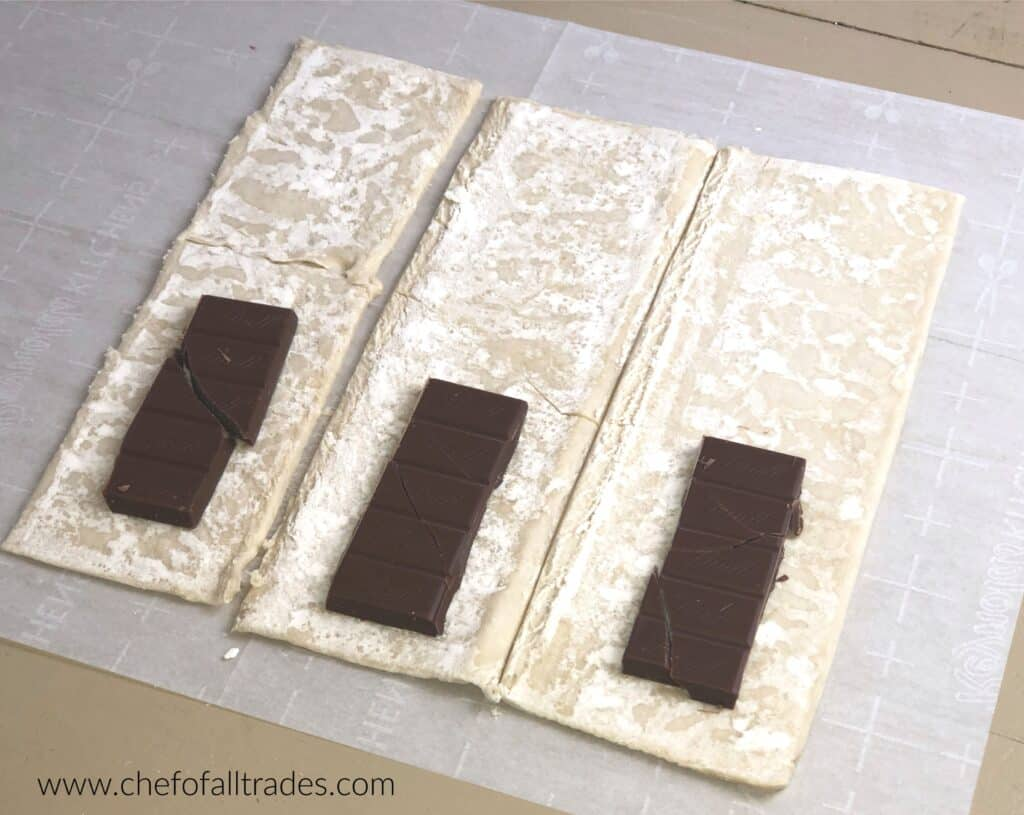 Sections of chocolate bar on bottom half of puff pastry