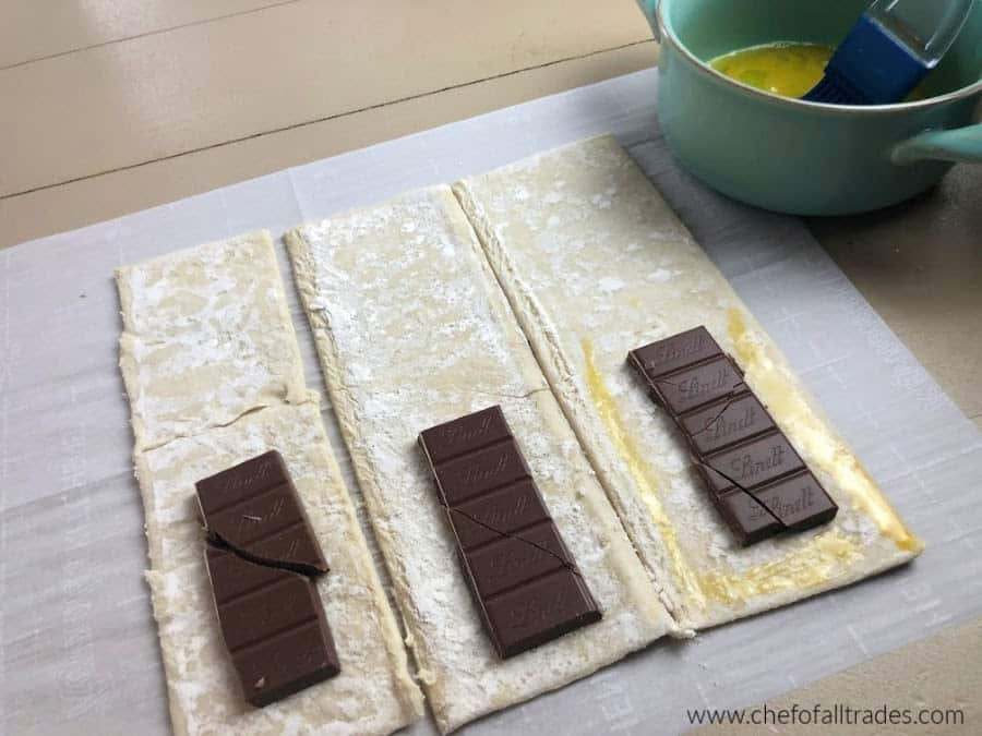puff pastry with chocolate on the bottom being brushed with egg wash