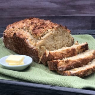 No Yeast Quick Bread on a green cloth with a few pads of butter in a white dish
