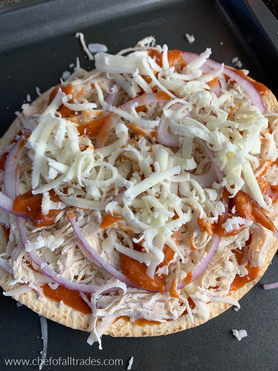 bbq chicken pizza on a baking sheet