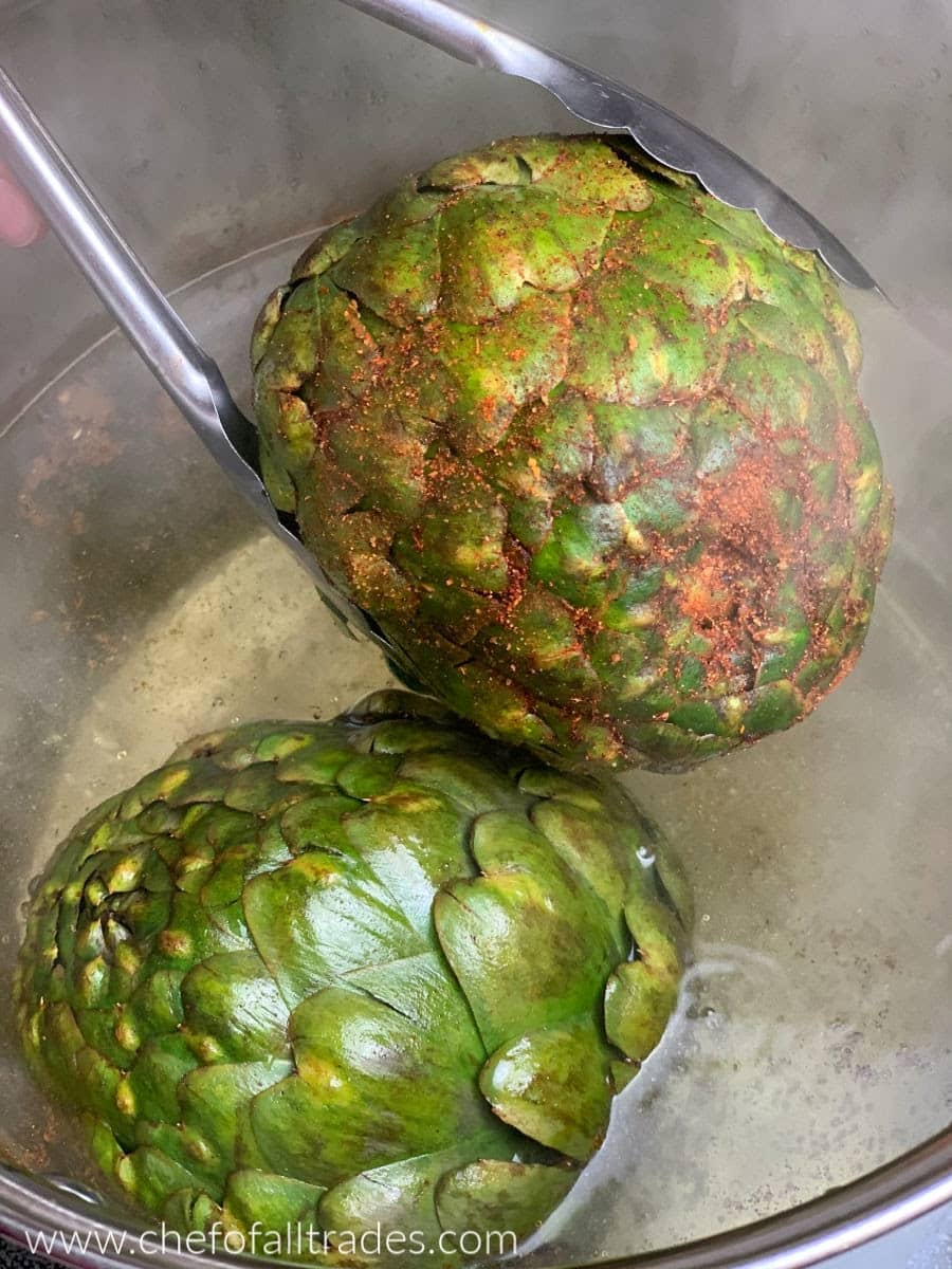 Placing the artichokes in boiling water