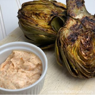Fire Roasted Cajun Artichokes on a cutting board with cajun mayo
