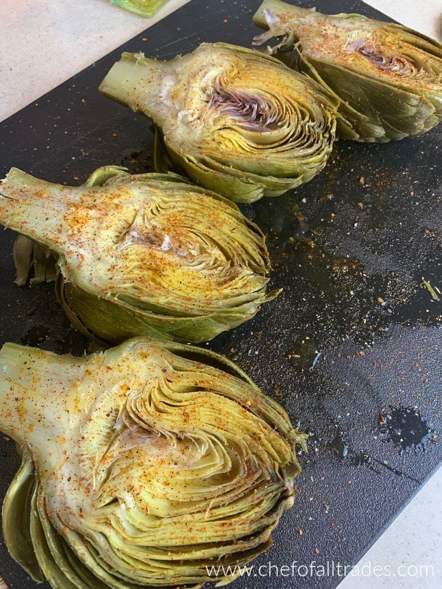 artichokes cut in half, oiled and seasoned on a cutting board