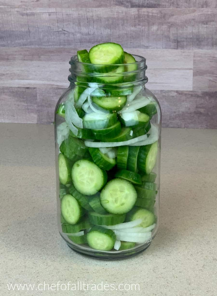 cucumbers and onions in a mason jar on a counter