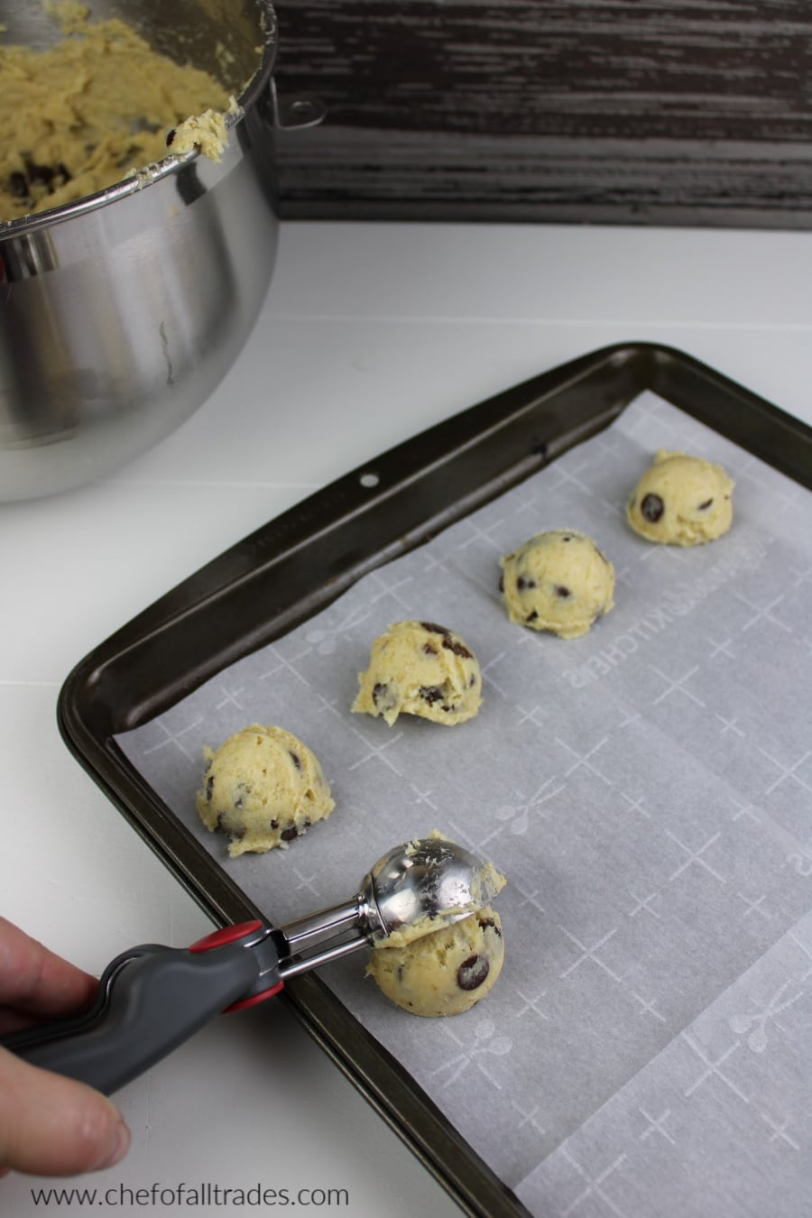 scooping the cookie dough on a cookie sheet with parchment paper