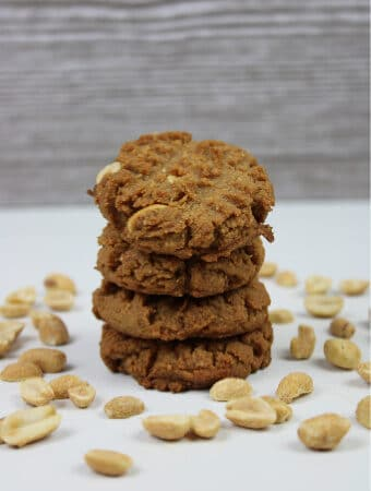 stack of peanut butter cookies surrounded by peanuts