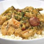 Cajun Chicken & Sausage Casserole over cauliflower rice in a white bowl