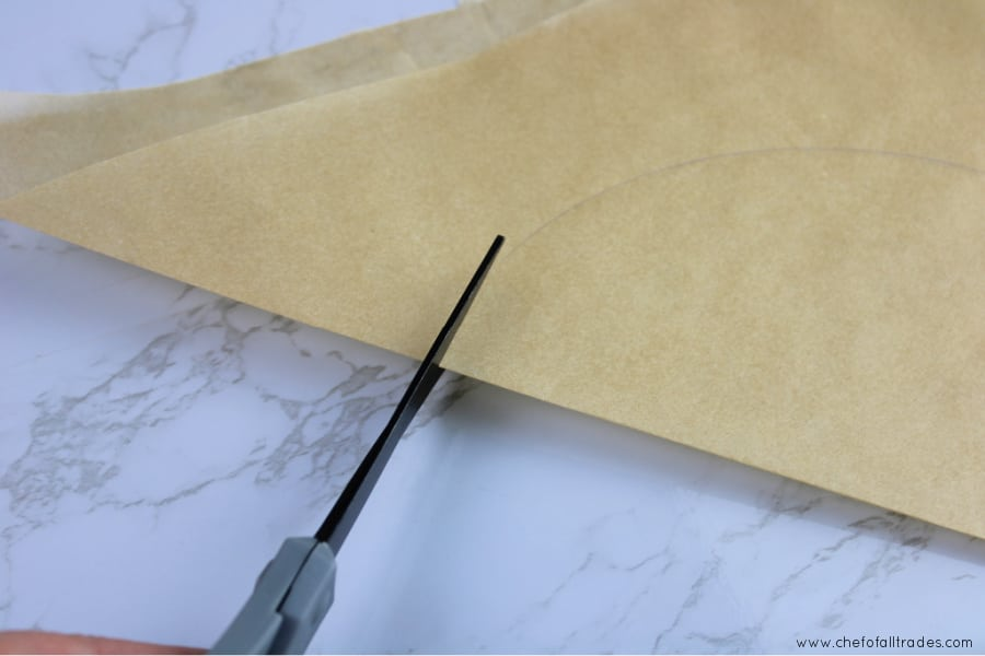 scissors cutting out the traced circle on the parchment