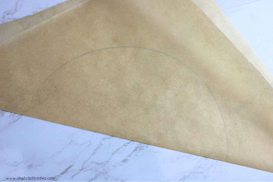 parchment paper folded in half to cut out the circle cake pan tracing