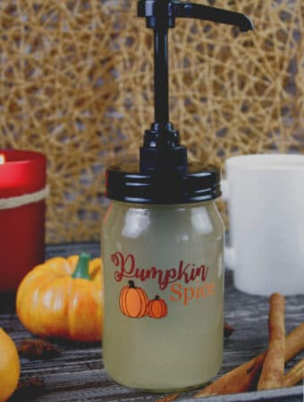 Sugar Free Pumpkin Spice Coffee Syrup in a mason jar with a pump surrounded by fall decorations