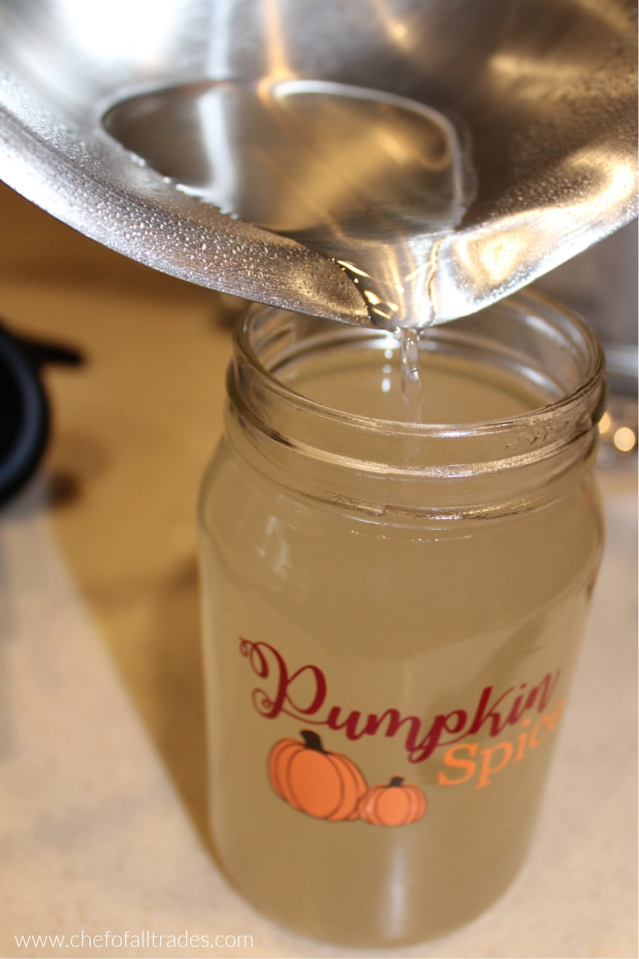 pouring syrup into a mason jar from the pot