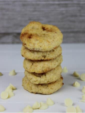 White Chocolate Macadamia Nut Cookies Stacked on a white table with white chocolate chips around