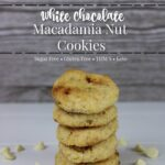 White Chocolate Macadamia Nut Cookies stacked on a white table with white chocolate chips surrounding the stack of cookies
