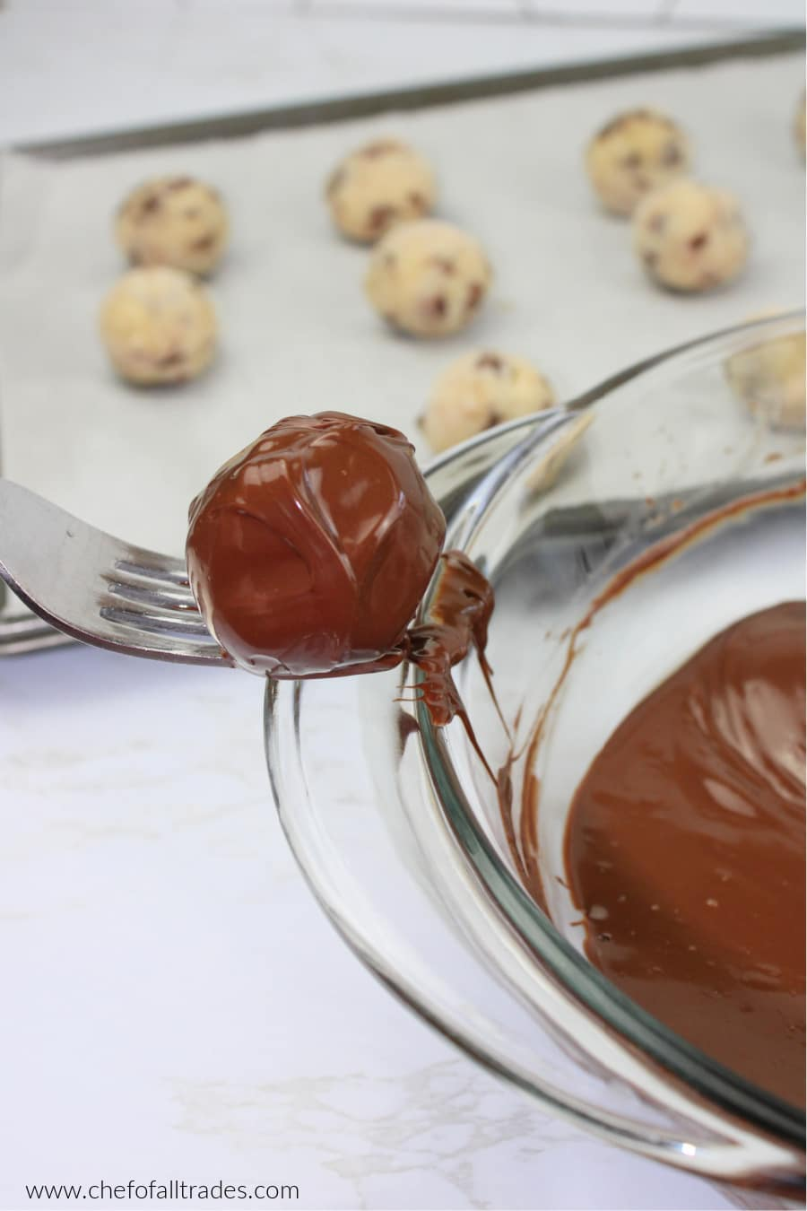 Chocolate Chip Cookie Dough Truffle on a fork scraping fork on edge of bowl