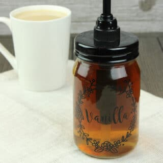 "vanilla coffee syrup in a glass jar with a pump attached. ""vanilla"" label is on the jar with a white cup of coffee in the background."