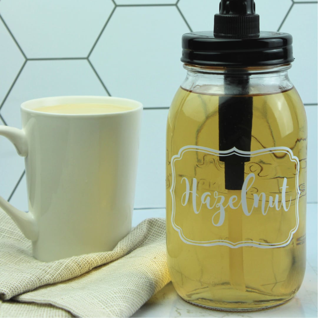 hazelnut coffee syrup in a mason jar with a cup of coffee in the background